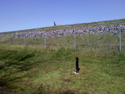 View of off-site permitter monitoring well casing, fenced site and landfill with landfill gas extraction well.