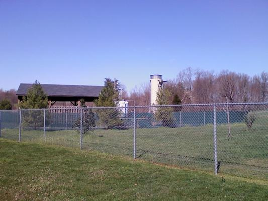 View of fenced site and landfill gas treatment building and flare unit.