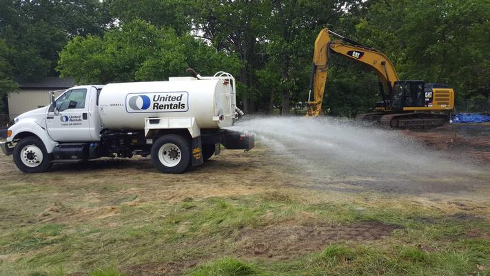 Water truck wetting the path of a bulldozer.