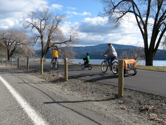 A family bicycles past Lake Coeur d'Alene. A fish consumption advisory is in effect for the lake.